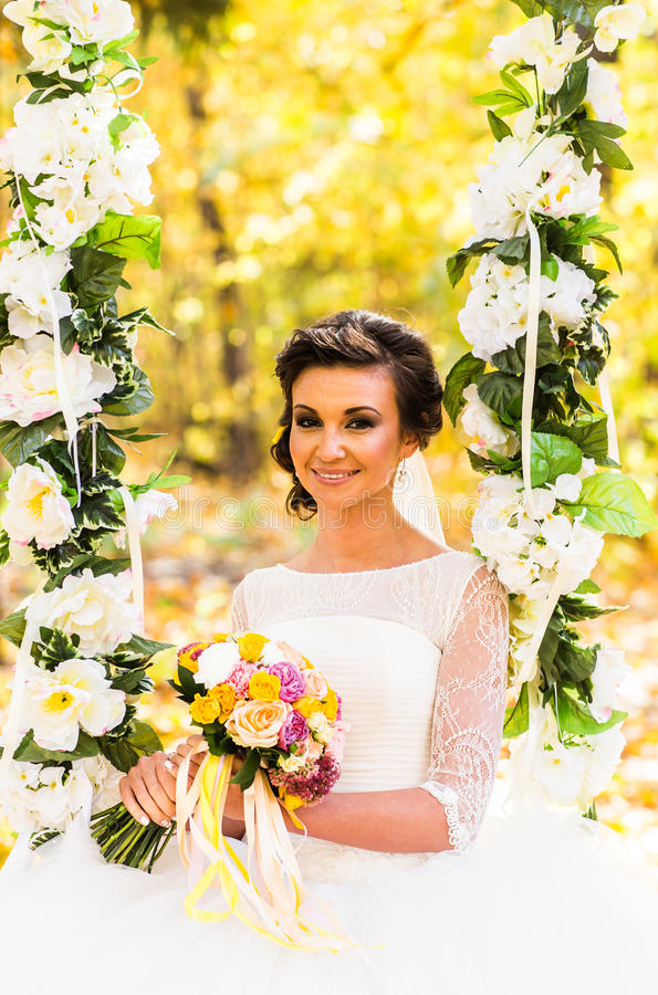 Η πανέμορφη νύφη κάθεται στην ταλάντευση σε ένα πάρκο φθινοπώρου στοκ φωτογραφίες με δικαίωμα ελεύθερης χρήσης
