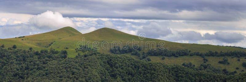 Η πανοραμική άποψη των σύννεφων επάνω από τους λόφους τοποθετεί πλησίον Elbrus στοκ φωτογραφία με δικαίωμα ελεύθερης χρήσης