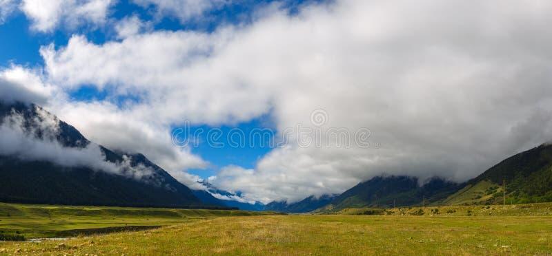Η πανοραμική άποψη των σύννεφων επάνω από τους λόφους τοποθετεί πλησίον Elbrus στοκ φωτογραφίες