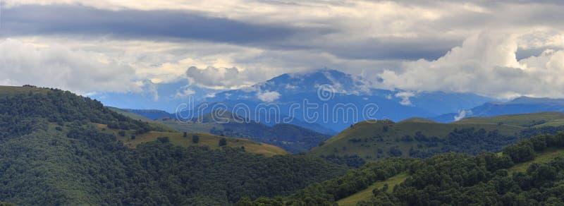 Η πανοραμική άποψη των σύννεφων επάνω από τους λόφους τοποθετεί πλησίον Elbrus στοκ φωτογραφία