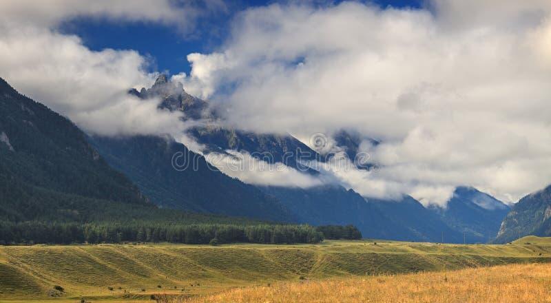 Η πανοραμική άποψη των σύννεφων επάνω από τους λόφους τοποθετεί πλησίον Elbrus στοκ εικόνα με δικαίωμα ελεύθερης χρήσης