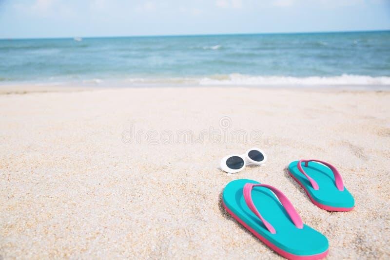 Η παντόφλα του ποδιού στα παπούτσια σανδαλιών και το μπλε ωκεάνιο κύμα ποτίζουν τη διανομή σε αμμώδη στοκ εικόνα με δικαίωμα ελεύθερης χρήσης