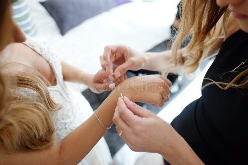 Η παράνυμφος βοηθά να βάλει ένα βραχιόλι στο βραχίονά του για τη νύφη στοκ φωτογραφία
