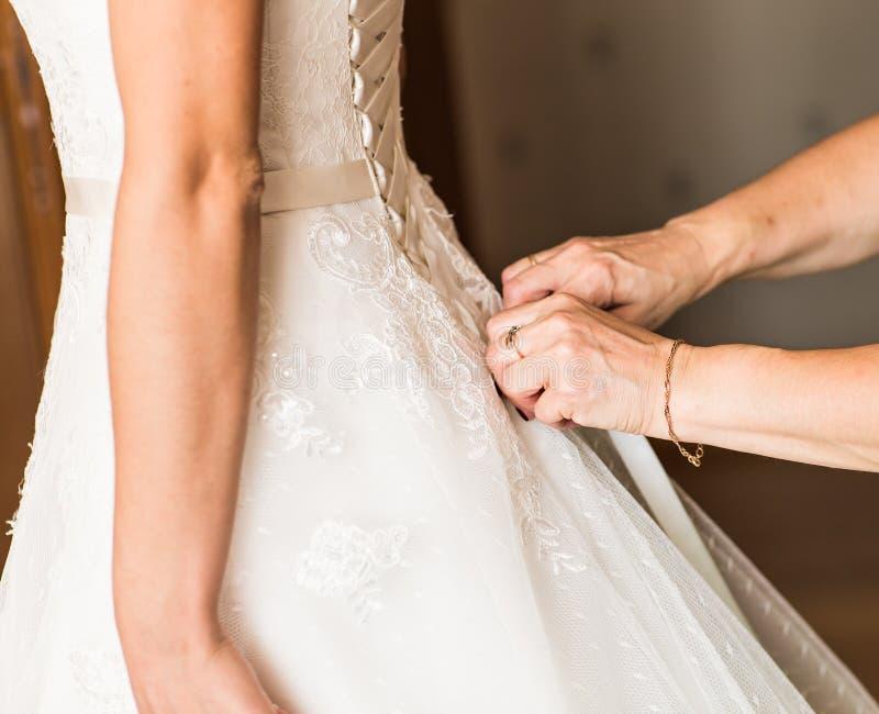 Η παράνυμφος βοηθά τη νύφη για να ντύσει στοκ εικόνες με δικαίωμα ελεύθερης χρήσης