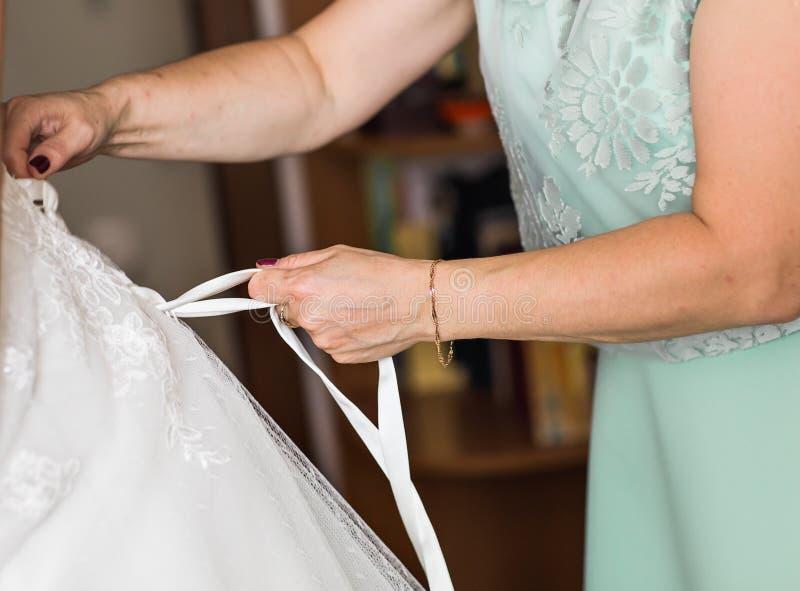 Η παράνυμφος βοηθά τη νύφη για να ντύσει στοκ εικόνες