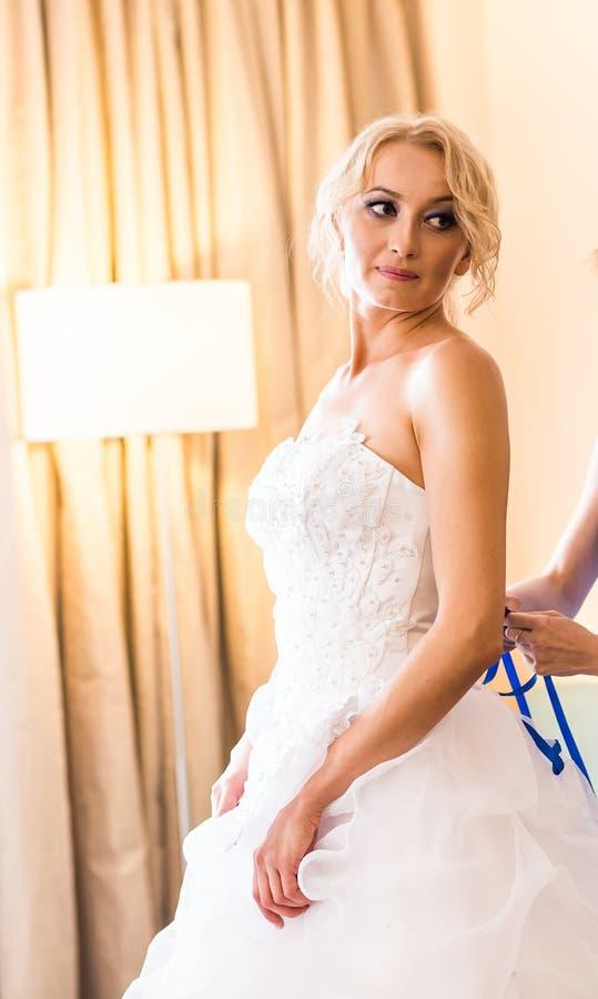 Η παράνυμφος βοηθά τη νύφη για να ντύσει στοκ εικόνα