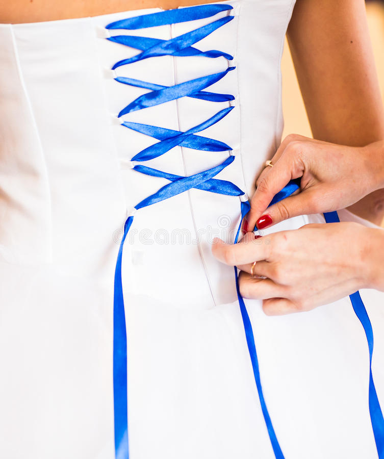 Η παράνυμφος βοηθά τη νύφη για να ντύσει στοκ φωτογραφία