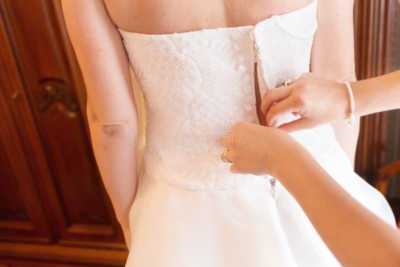 Η παράνυμφος βοηθά τη νύφη στο κούμπωμα του γαμήλιου φορέματος στοκ εικόνα