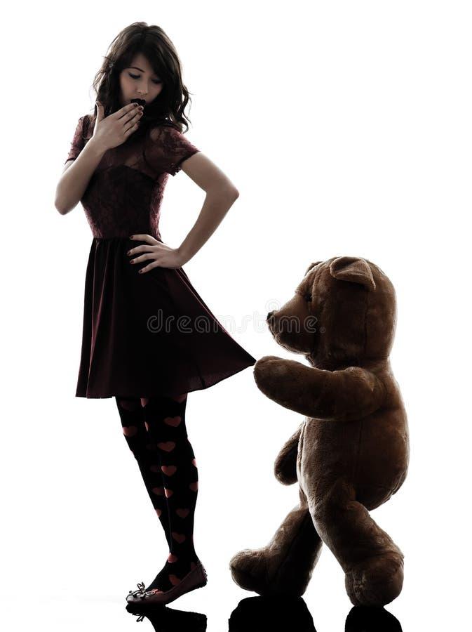 Η παράξενη νέα γυναίκα και κακοήθης teddy αντέχουν τη σκιαγραφία στοκ εικόνες