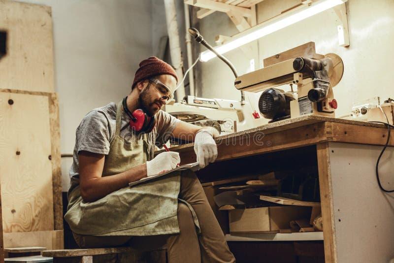 Η παραγωγή βιοτεχνών σκιαγραφεί κοντά στον πάγκο εργασίας στοκ φωτογραφίες