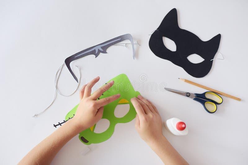 Η παραγωγή καλύπτει τη μάσκα τεράτων ` s αποκριών διακοπών εγγράφου μαύρα χέρια γατών τοπ άποψη στοκ φωτογραφία