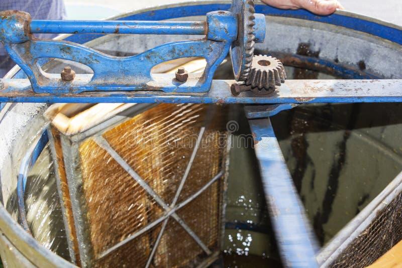 Η παραγωγή του μελιού από την κηρήθρα φυσικό στάλαγμα μελιού Ένας παλαιός εξολκέας μελιού στοκ εικόνα