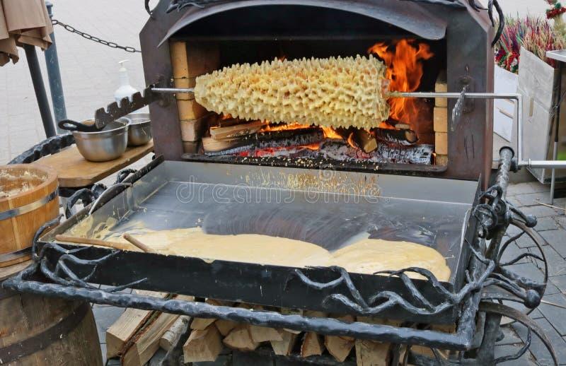 Η παραδοσιακή λιθουανική πίτα Shakotis που ψήνεται ανοίγει πυρ από τους κτυπημένους λέκιθους αυγών στοκ εικόνες