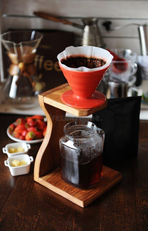 Η παρασκευή καφέ στο κόκκινο χύνει στον ξύλινο σταθμό καφέ Συσκευές για τη χειρωνακτική παρασκευή στο υπόβαθρο στοκ εικόνα με δικαίωμα ελεύθερης χρήσης