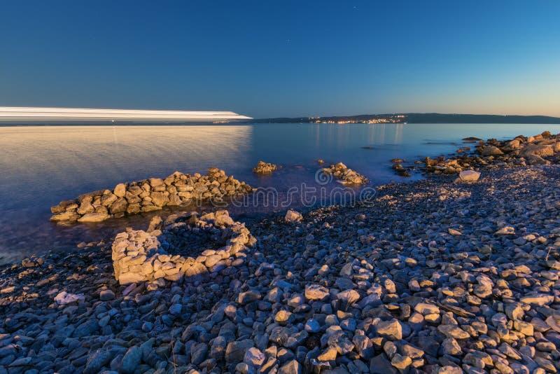 Η παραλία με τις δομές και τη διάβαση πετρών της βάρκας ανάβει τη νύχτα στοκ φωτογραφία