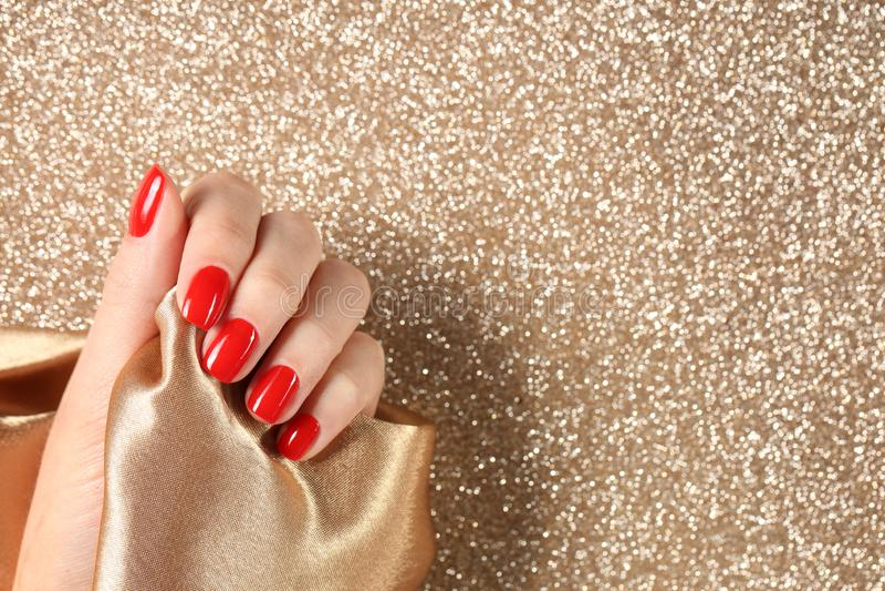 Η παρουσίαση γυναικών το χέρι με την κόκκινη στιλβωτική ουσία καρφιών στο υπόβαθρο χρώματος, τοπ άποψη στοκ φωτογραφία με δικαίωμα ελεύθερης χρήσης