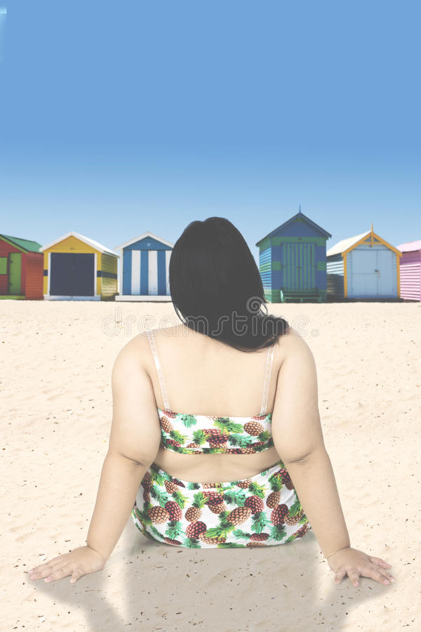 Η παχύσαρκη γυναίκα κάθεται στην ακτή στοκ φωτογραφία