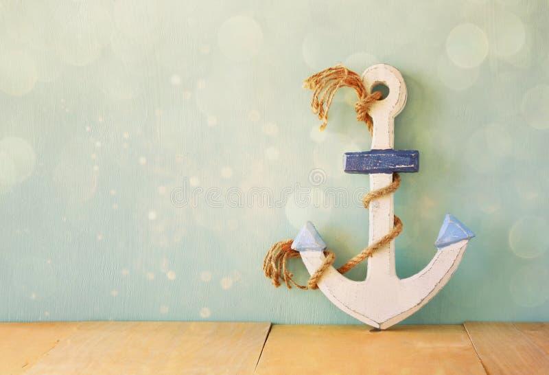 Η παλαιά ναυτική άγκυρα στον ξύλινο πίνακα πέρα από το ξύλινο υπόβαθρο aqua και ακτινοβολεί επικάλυψη στοκ φωτογραφία με δικαίωμα ελεύθερης χρήσης