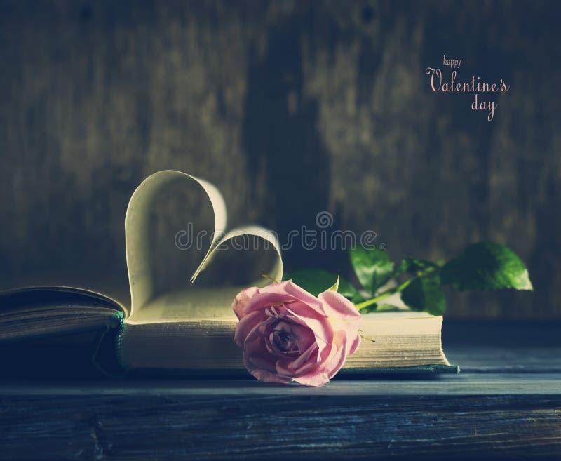 Η παλαιά σελίδα βιβλίων με καρδιά-διαμορφωμένο ημερησίως βαλεντίνων ` s και έναν ρόδινο αυξήθηκε στοκ εικόνα