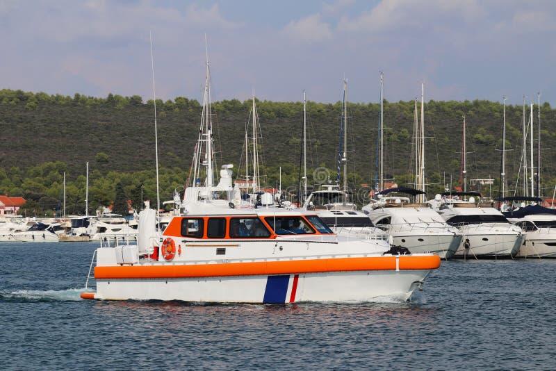 Η πειραματική βάρκα πλέει τα νερά της μαρίνας μεταξύ των δεμένων πλέοντας γιοτ Βοήθεια στην πρόσδεση του σκάφους στο θαλάσσιο λιμ στοκ εικόνα με δικαίωμα ελεύθερης χρήσης