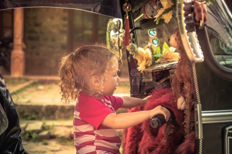 Η περίεργη οδηγώντας tuk tuk μοτοσικλέτα κοριτσιών τουριστών παιδιών κατά τη διάρκεια των παιδιών έννοιας της Ασίας Ταϊλάνδη ταξι στοκ εικόνες