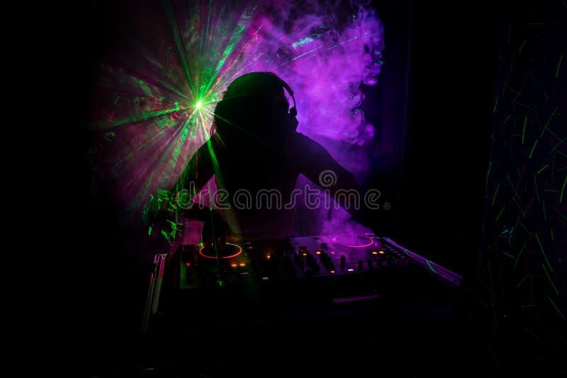 Η περιστροφή του DJ, η μίξη, και το γρατσούνισμα σε μια λέσχη νύχτας, χέρια των διάφορων ελέγχων διαδρομής τσιμπημάτων του DJ στη στοκ εικόνα