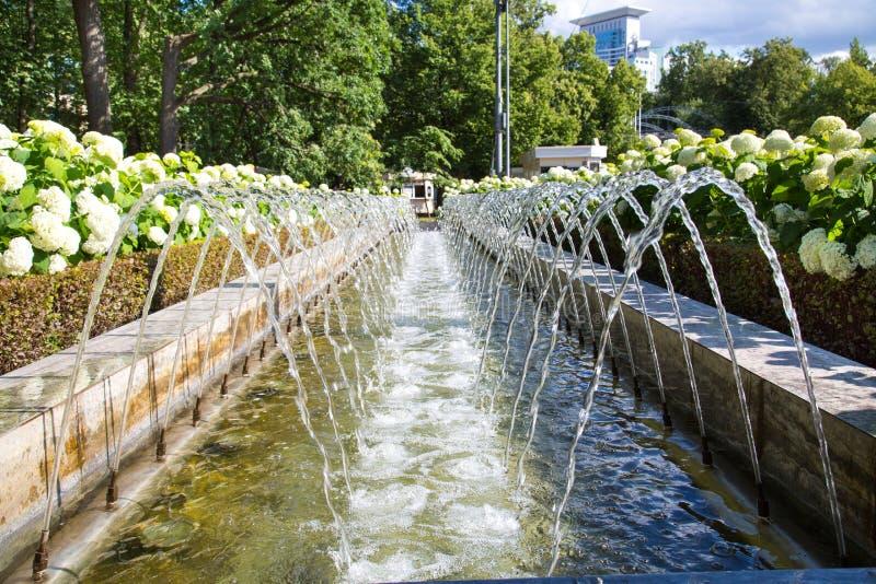 Η πηγή είναι αστική υπό μορφή καναλιού προβολών ύδατος και στις δύο πλευρές στοκ φωτογραφία