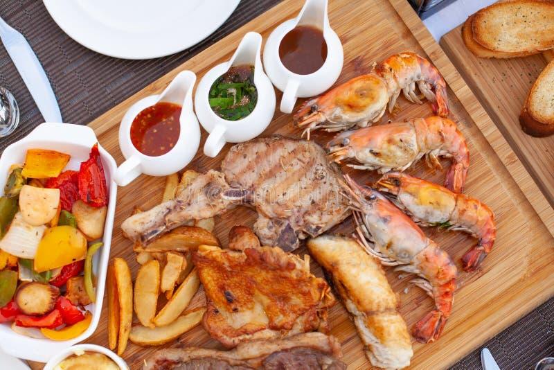 Η πιατέλα κρέατος εξυπηρέτησε με τη σαλάτα, τα τηγανητά και το κόκκινο κρασί με την επιλογή τρία της σάλτσας στον ξύλινο φραγμό σ στοκ εικόνες