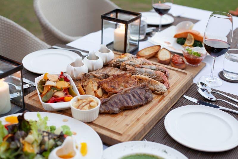 Η πιατέλα κρέατος εξυπηρέτησε με τη σαλάτα, τηγανητά με την επιλογή τρία της σάλτσας στον ξύλινο φραγμό στο λεπτό να δειπνήσει επ στοκ εικόνα με δικαίωμα ελεύθερης χρήσης
