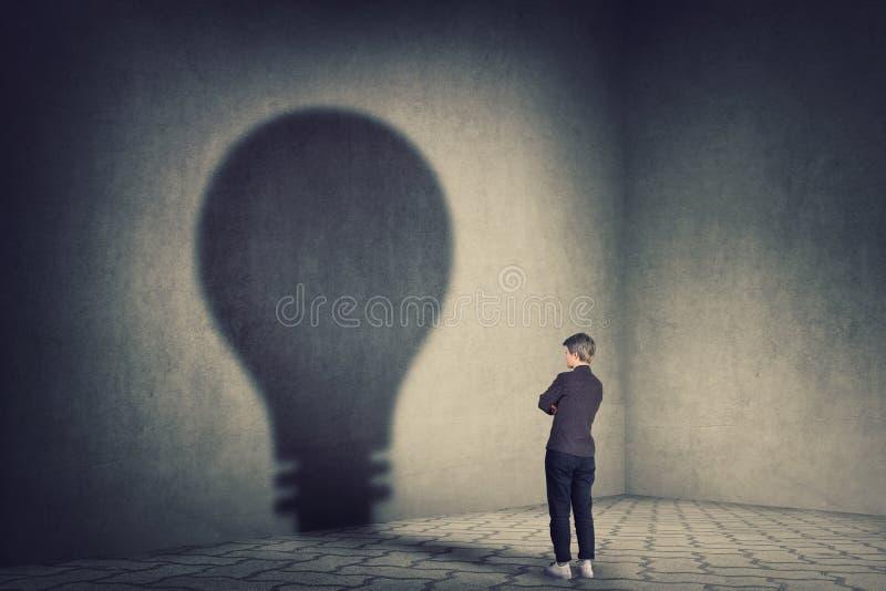 Η πλήρης εκμετάλλευση επιχειρηματιών μήκους νέα δίνει διπλωμένος πετώντας μια σκιά μορφής λαμπών φωτός στον τοίχο Ιδέα φιλοδοξίας στοκ εικόνα