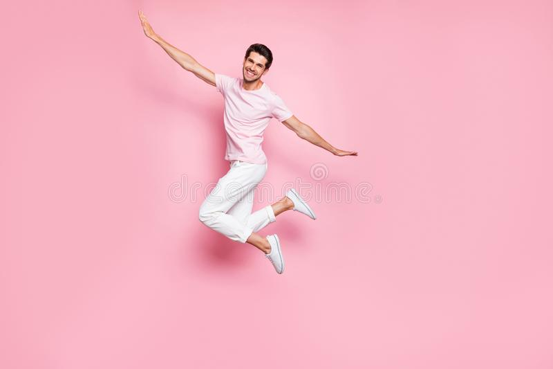 Η πλήρης φωτογραφία μήκους του όμορφου ατόμου που αυξάνει το χαμόγελο όπλων χεριών που πηδά φορώντας την άσπρη μπλούζα ασθμαίνει  στοκ φωτογραφίες