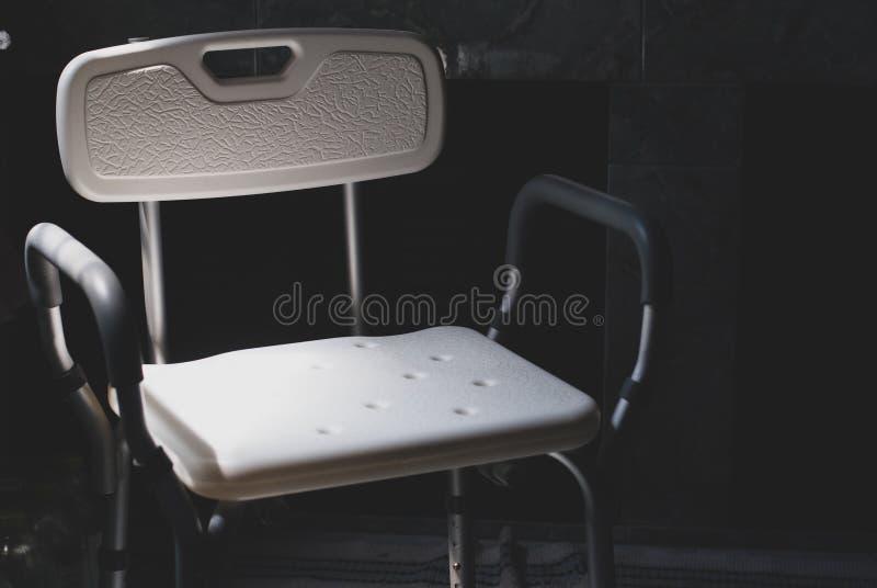 Η πλαστική καρέκλα λουσίματος για τα παλαιότερα ή με ειδικές ανάγκες άτομα που πλημμυρίζουν υπόβαλε το σκοτάδι αφήνοντας το φως π στοκ εικόνα