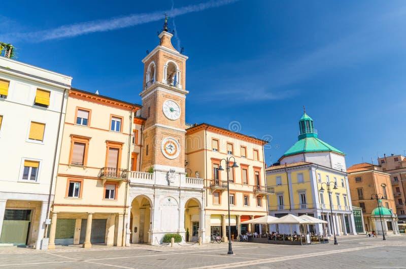 Η πλατεία Tre Martiri τρεις μάρτυρες τακτοποιεί με τα παραδοσιακά κτήρια με τον πύργο ρολογιών και κουδουνιών σε Rimini στοκ εικόνα