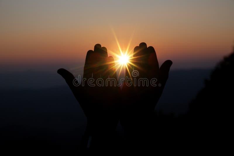 Η πνευματική προσευχή παραδίδει τον ήλιο λάμπει με το θολωμένο όμορφο υπόβαθρο ηλιοβασιλέματος στοκ εικόνα