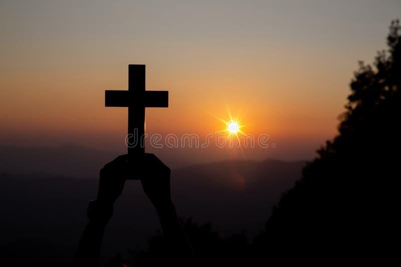 Η πνευματική προσευχή παραδίδει τον ήλιο λάμπει με το θολωμένο όμορφο υπόβαθρο ηλιοβασιλέματος στοκ φωτογραφίες