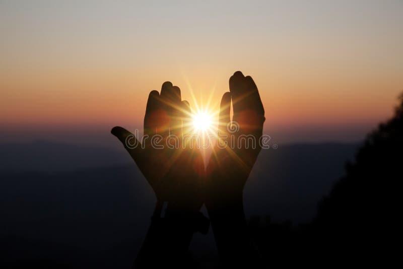 Η πνευματική προσευχή παραδίδει τον ήλιο λάμπει με το θολωμένο όμορφο υπόβαθρο ηλιοβασιλέματος στοκ εικόνες