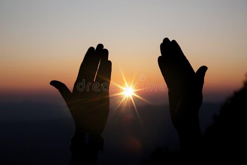 Η πνευματική προσευχή παραδίδει τον ήλιο λάμπει με το θολωμένο όμορφο υπόβαθρο ηλιοβασιλέματος στοκ εικόνα με δικαίωμα ελεύθερης χρήσης