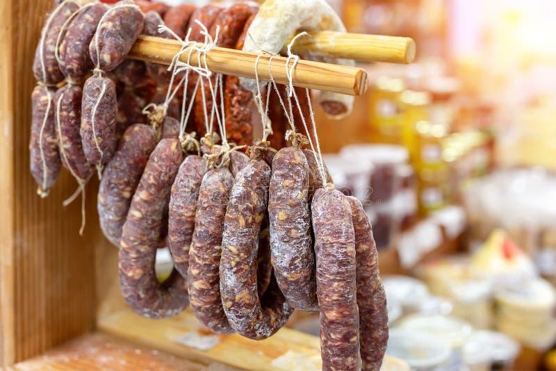 Η ποικιλία των εύγευστων ξηρών λουκάνικων κρέμασε στο ξύλινο ράφι στην τοπική αγορά αγροτών Φρέσκες νόστιμες λιχουδιές κρέατος στ στοκ εικόνες