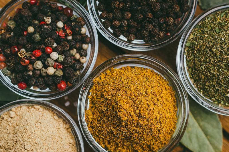 Η ποικιλία των καρυκευμάτων στο στρογγυλό γυαλί κυλά - αλεσμένη πιπερόριζα, λυκίσκος-suneli, Kari, μαύρο πιπέρι και ένα μίγμα στοκ φωτογραφία