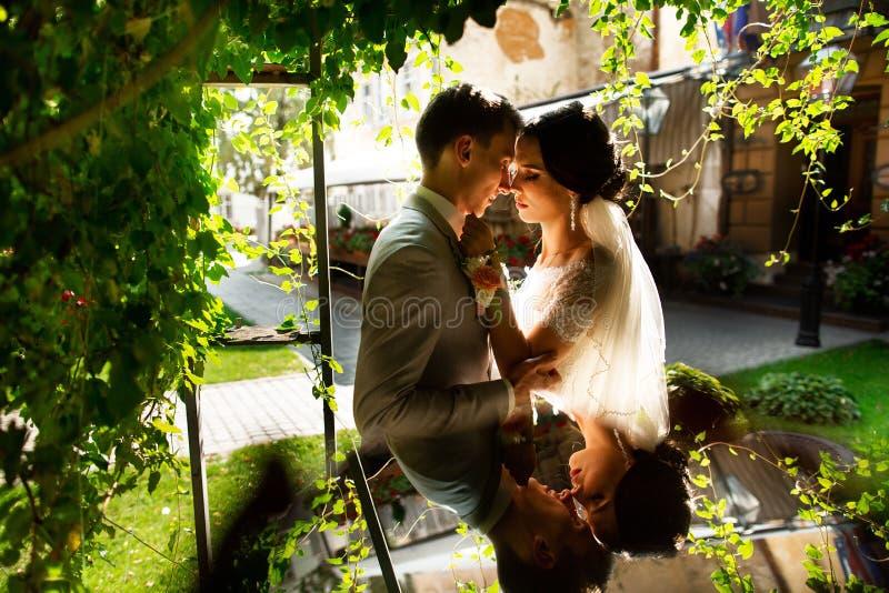 Η πολυτέλεια πάντρεψε το γαμήλιους ζεύγος, τη νύφη και το νεόνυμφο, που θέτουν στο ρομαντικό προαύλιο της παλαιάς πόλης στοκ φωτογραφία