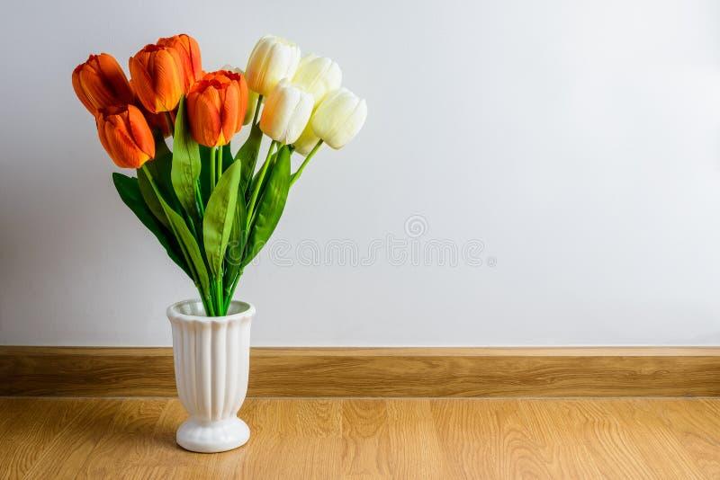 Η πορτοκαλιά, άσπρη τουλίπα ανθίζει την ανθοδέσμη στο βάζο στο ξύλινο πάτωμα στο φ στοκ εικόνες με δικαίωμα ελεύθερης χρήσης