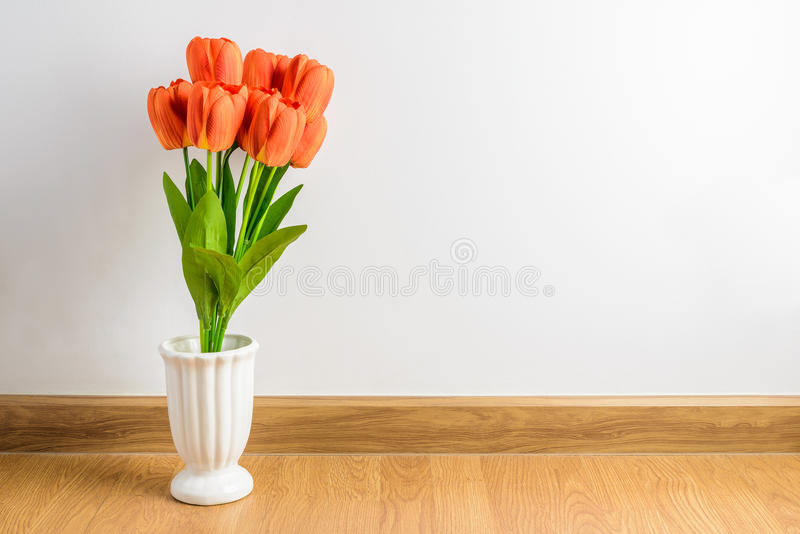 Η πορτοκαλιά τουλίπα ανθίζει την ανθοδέσμη στο βάζο στο ξύλινο πάτωμα μπροστά από στοκ εικόνες με δικαίωμα ελεύθερης χρήσης