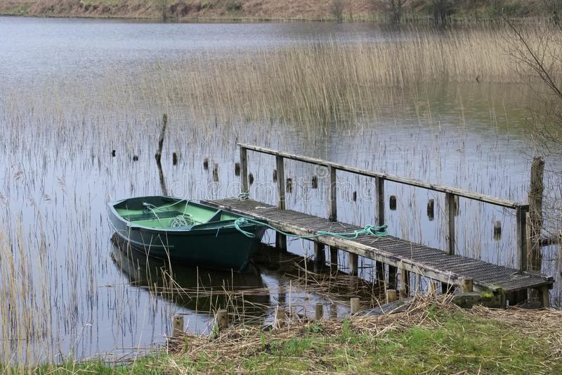 Η πράσινη βάρκα κωπηλασίας έδεσε με το σχοινί στην ξύλινη αποβάθρα λιμ στοκ φωτογραφία με δικαίωμα ελεύθερης χρήσης