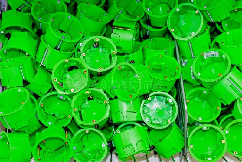 Η πράσινη πλαστική στρογγυλή υποδοχή διακοπτών, τοποθετεί το κιβώτιο τοίχων για την καλωδίωση στοκ φωτογραφία
