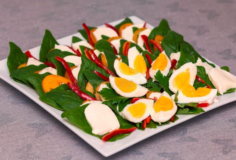 Η πράσινη σαλάτα με το κόκκινο πιπέρι αυγών σπανακιού, την ντομάτα και το τυρί στο άσπρο πιάτο, στο γκρίζο τραπεζομάντιλο με τις  στοκ φωτογραφία με δικαίωμα ελεύθερης χρήσης