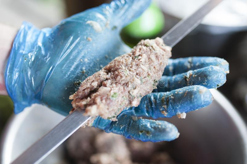 Η προετοιμασία ενός shish kebab, χέρι βάζει σε ένα kebab σε ένα οβελίδιο στοκ εικόνα με δικαίωμα ελεύθερης χρήσης