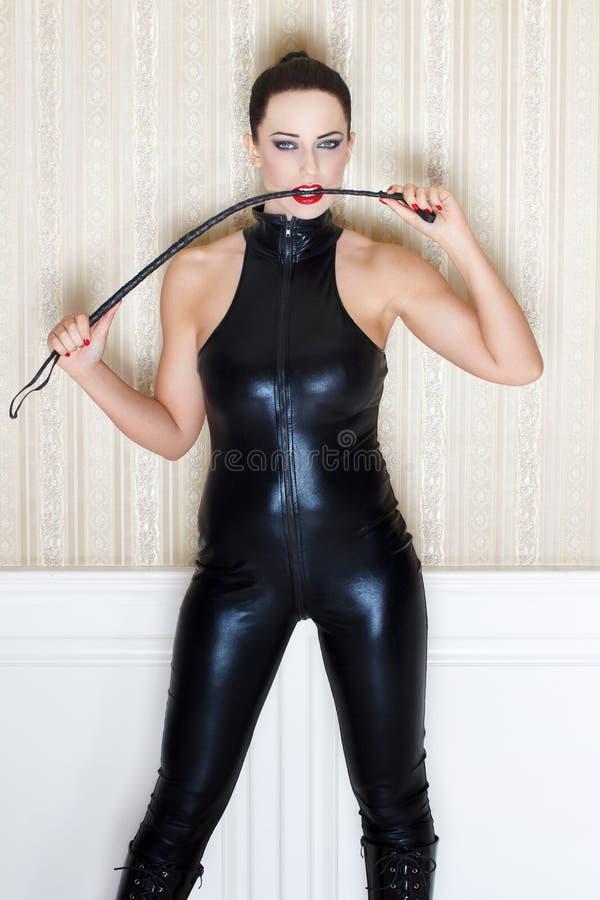 Η προκλητική γυναίκα στο δάγκωμα λατέξ catsuit κτυπά στοκ φωτογραφία