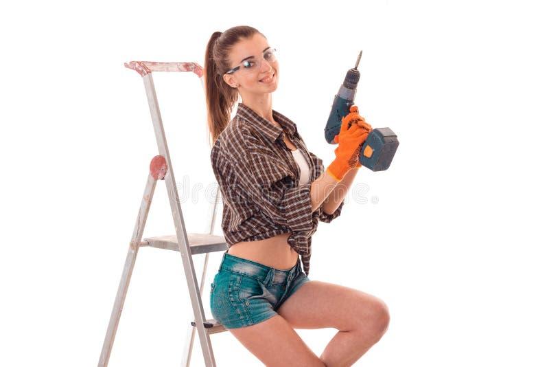 Η προκλητική κυρία brunette κάνει να ανανεώσει ένα διαμέρισμα με το τρυπάνι στα χέρια και τη σκάλα που απομονώνεται στο άσπρο υπό στοκ εικόνες με δικαίωμα ελεύθερης χρήσης