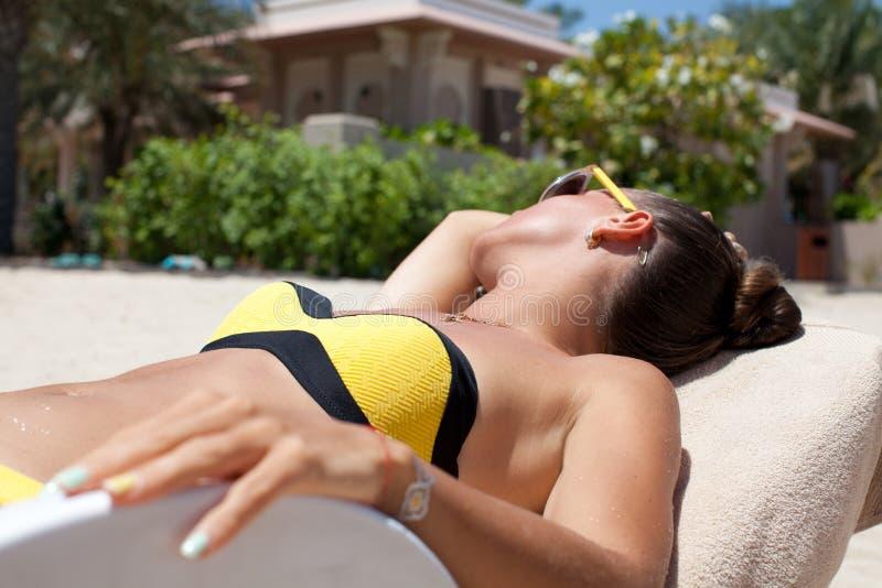 Η προκλητική χαλάρωση γυναικών μπικινιών suntan, που βάζει στο α στο tro στοκ εικόνα