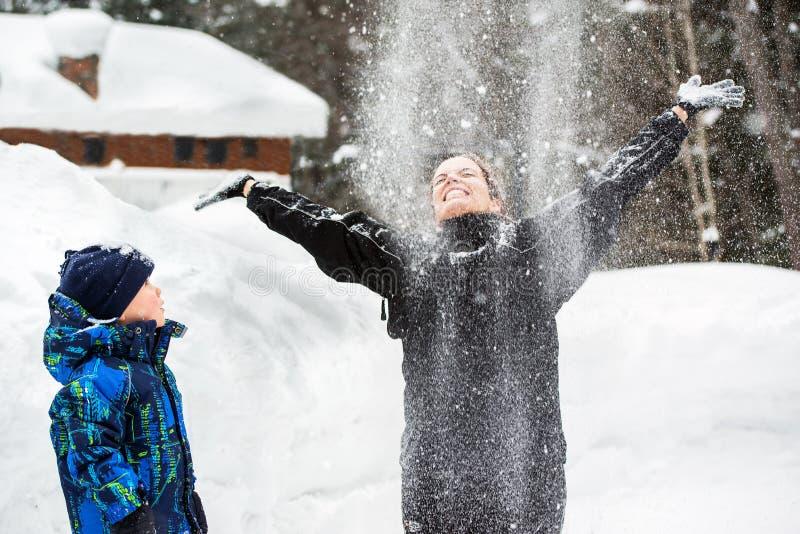 Η προσέχοντας μητέρα γιων ρίχνει το χιόνι επάνω στον αέρα στοκ φωτογραφία με δικαίωμα ελεύθερης χρήσης